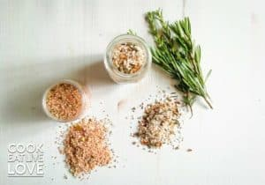 Homemade herb salt blends are in jars to give away and shown in small pile on background as well.