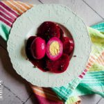 Plate of pickled beets and eggs on multicolored napkin and white plate.