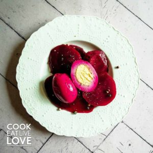 Fresh pickled beets and eggs on white plate.