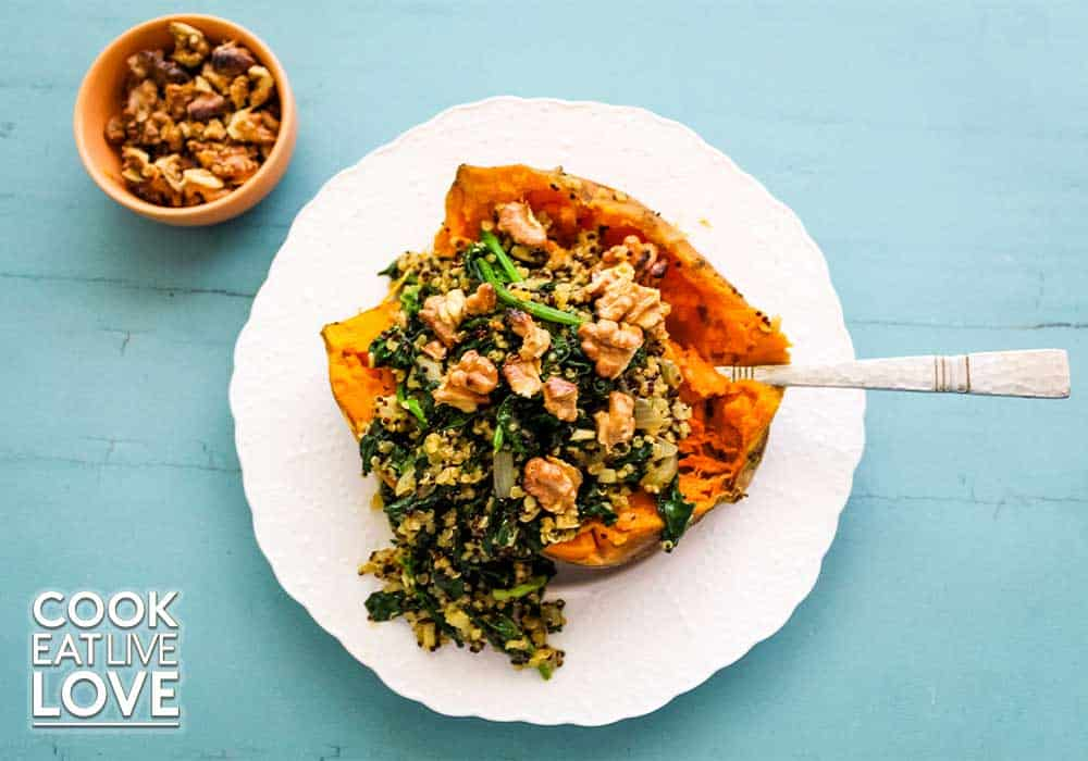 Quinoa spinach sweet potato topped with walnuts and served on white plate and blue background.