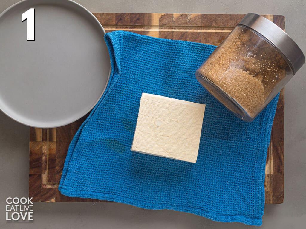 Pressing the tofu to make crispy baked tofu