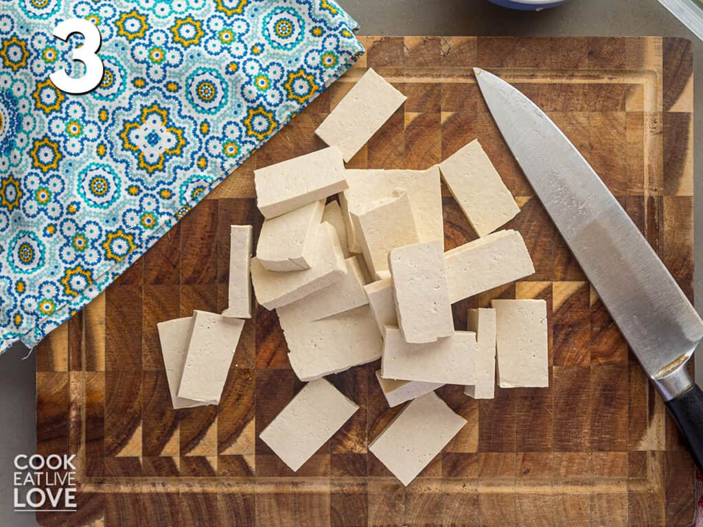 Tofu cut into pieces on a cutting board