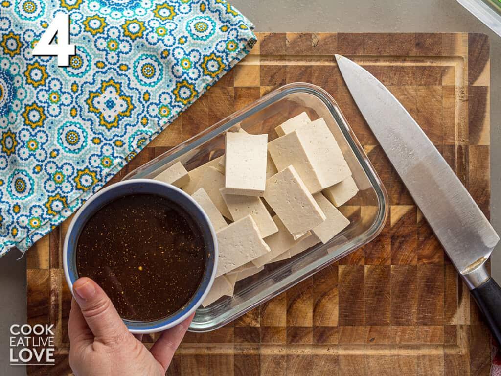 Adding the marinade to the cut tofu
