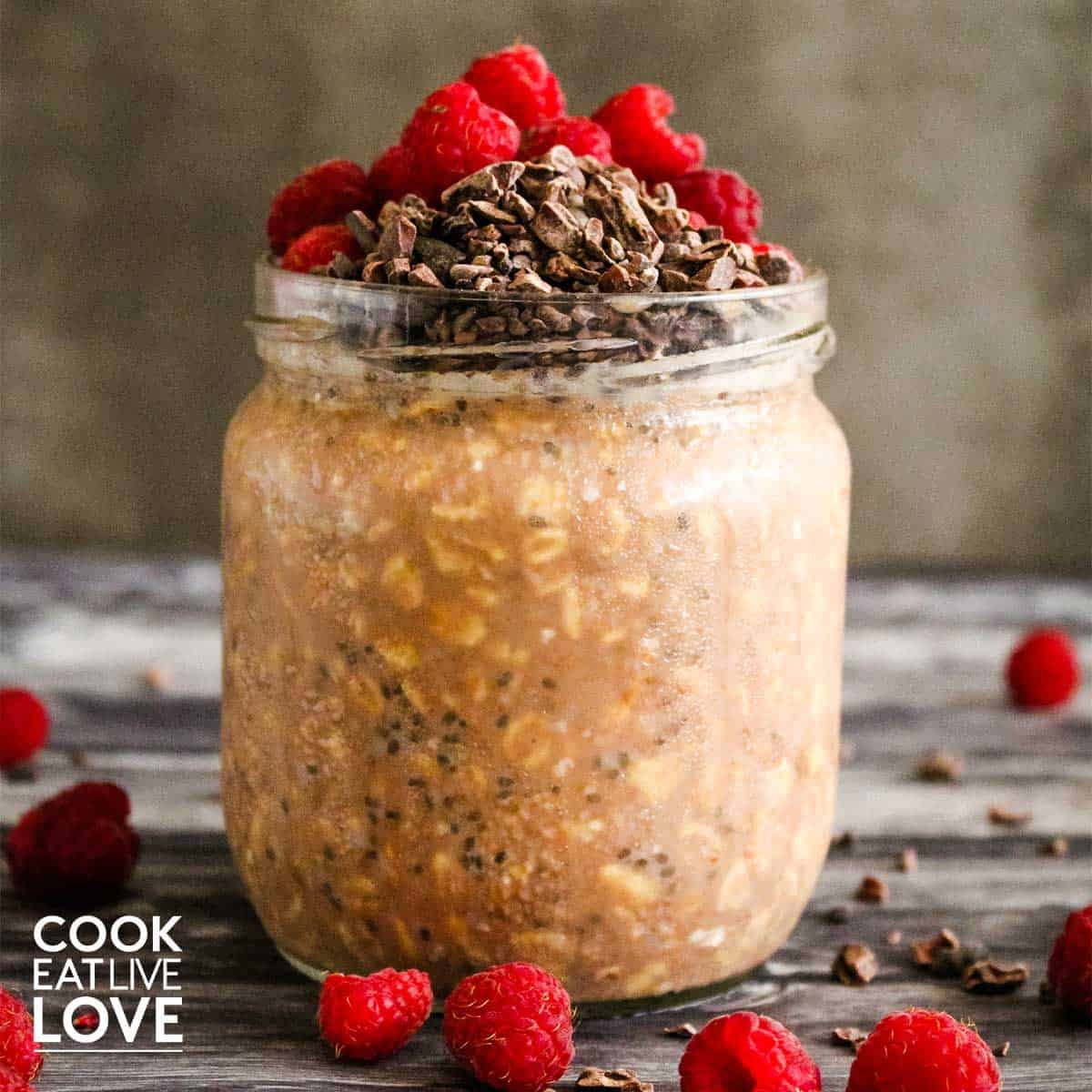Chocolate raspberry overnight oats are ready to eat in a jar.