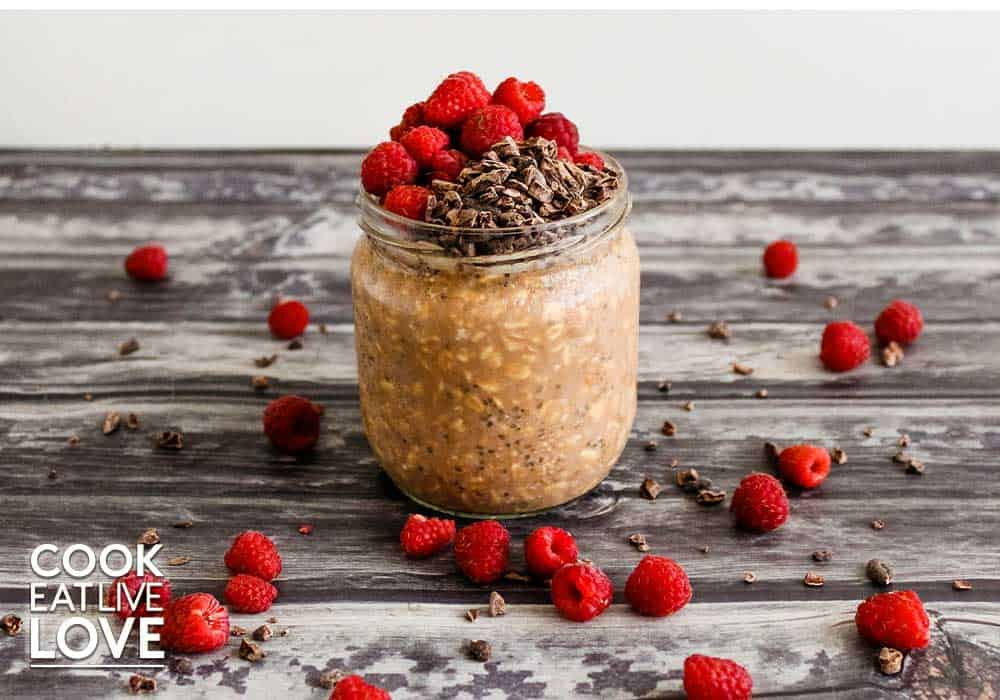 Chocolate overnight oats are topped with cacao nibs and fresh raspberries and some spilling out around it on the countertop.