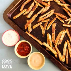 Baked fries on a baking sheet with sauces