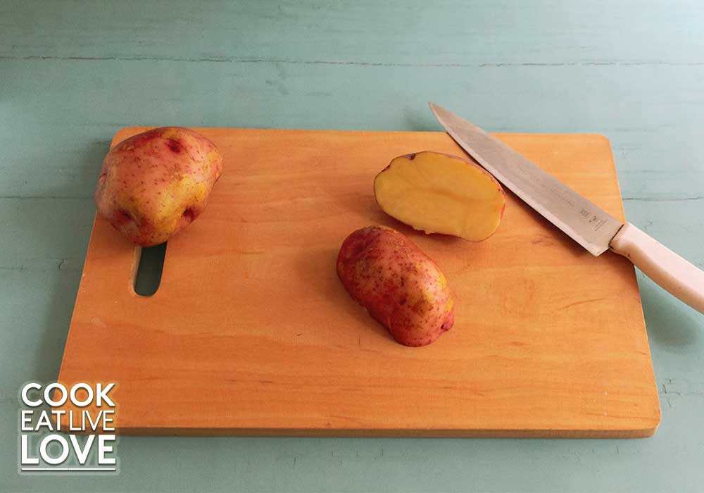 Potato for oven baked fries is shown cut in half with flat surface on cutting board.