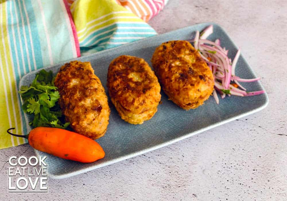 Papa rellena peruana are served up on a blue rectangle plate along with a serving of salsa criolla.