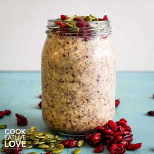 Glass jar of overnight oats with pumpkin seeds and cranberries