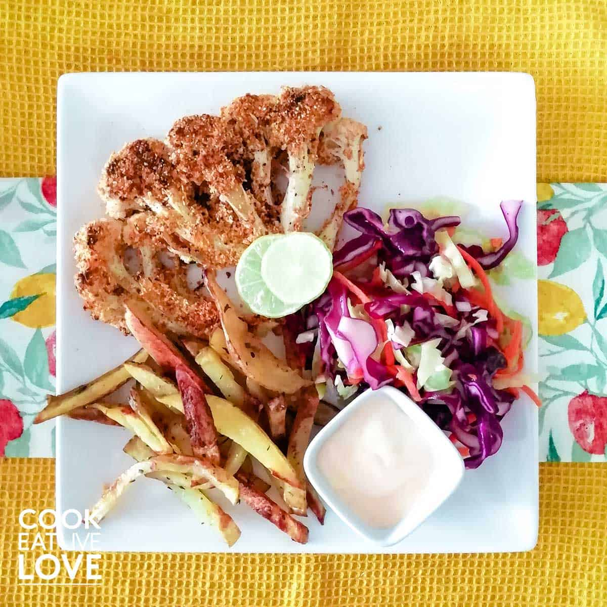 Plate of baked breaded cauliflower with fries and slaw.
