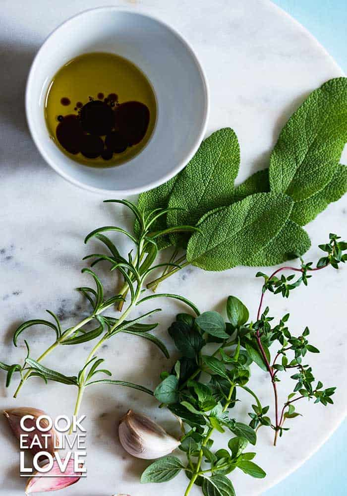 Photo of herbs and olive oil, a healthy fat on white-gray marble.