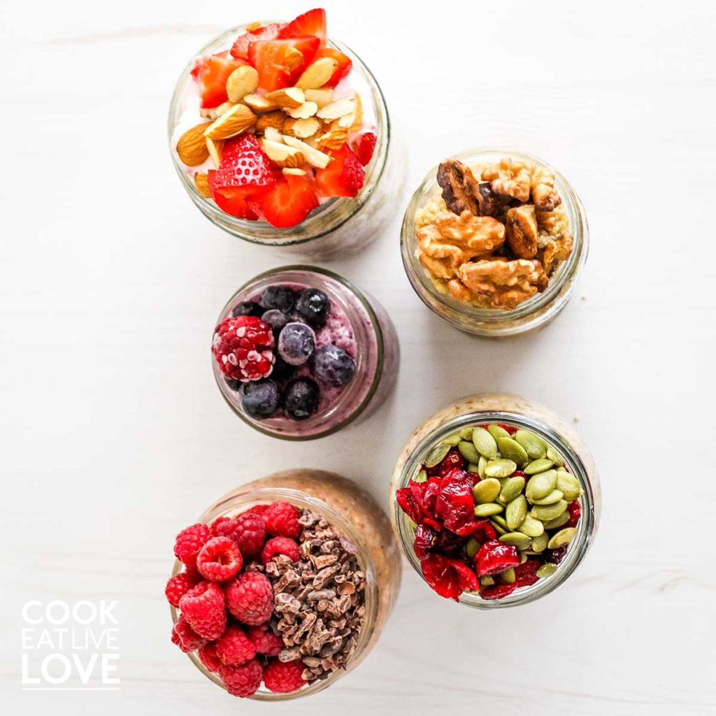 Oats and parfaits on table with fruit, nut and seeds