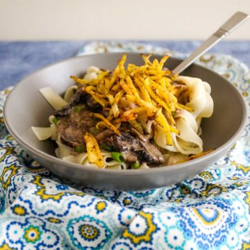 Vegetarian stroganoff is served up in gray bowl over noodles and topped with crispy matchstick potatoes.