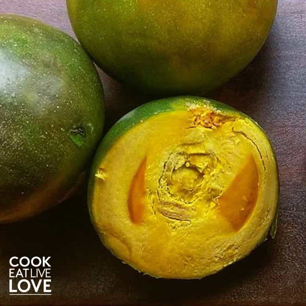 Lucuma fruit shown cut in half and whole. The whole are dark green while the flesh of the cut one is bright yellow-orange.
