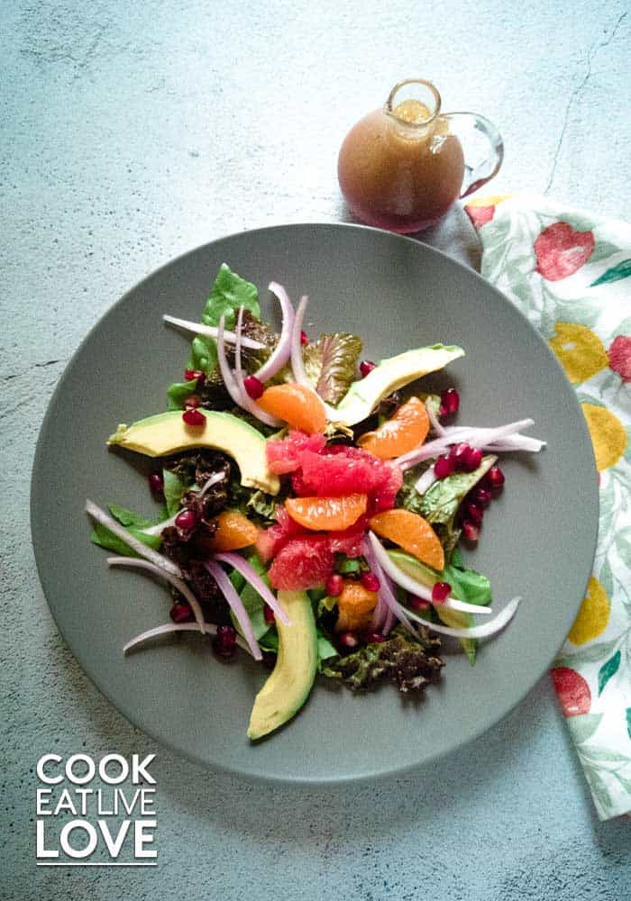 Photo of pomegranate salad with citrus fruits and avocado plus a small glass jar with pomegranate vinaigrette.
