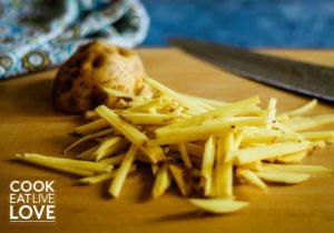 Potato for vegetarian stroganoff is cut into thin strips.