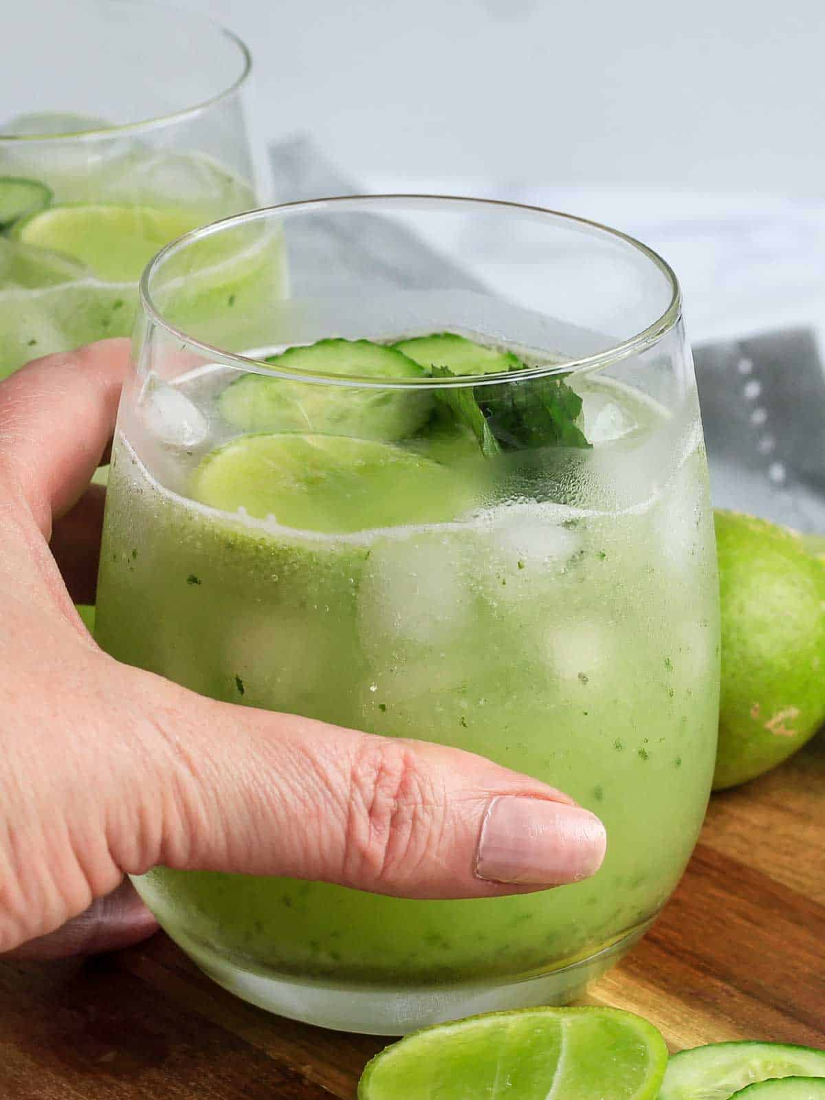 Hand reaching for a glass of cucumber spritzer