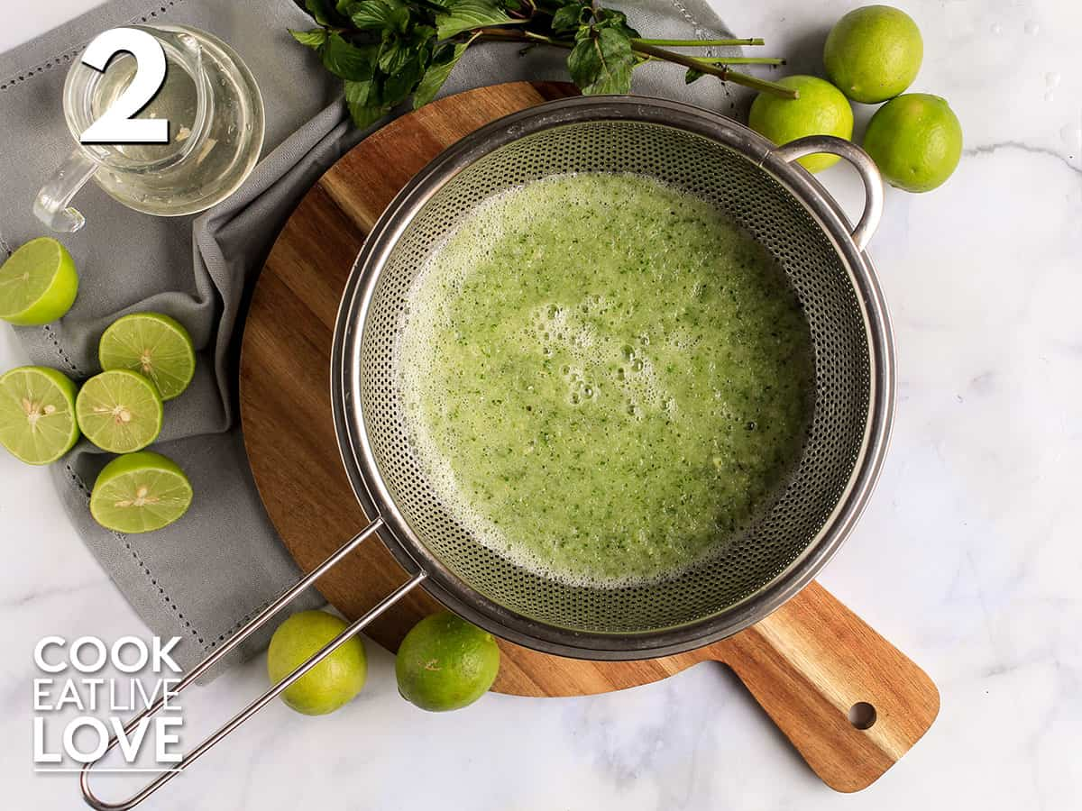 Straining the solids after blending to make cucumber drinks
