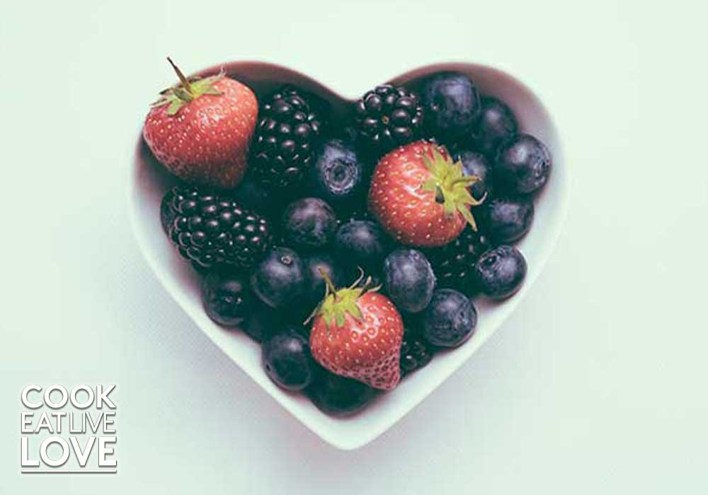 Photo of berries in a heart shaped dish on light green background