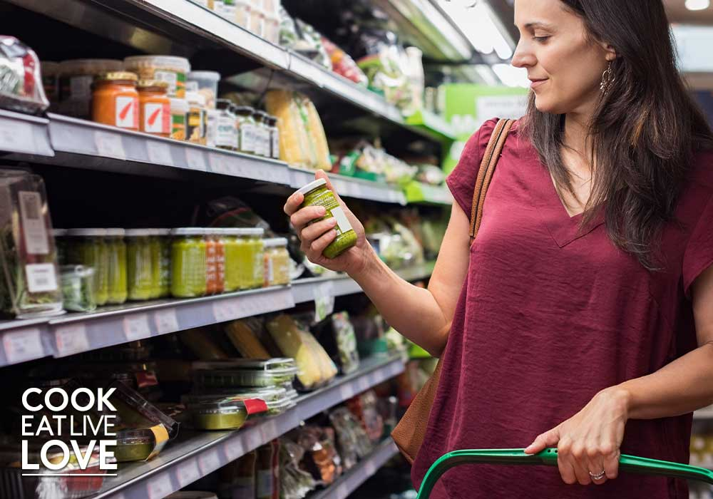 Woman in grocery store holding a jar and looking at the label.