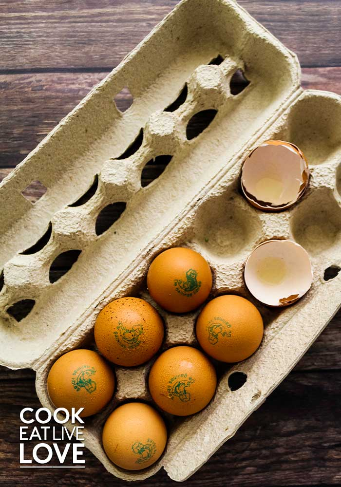 Carton of eggs half full with two empty egg shells.