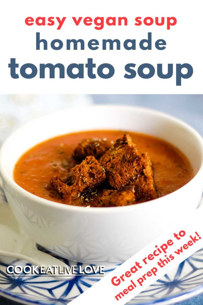 Photo of homemade tomato soup in a white bowl sitting on a white and blue plate. Garnished with croutons.