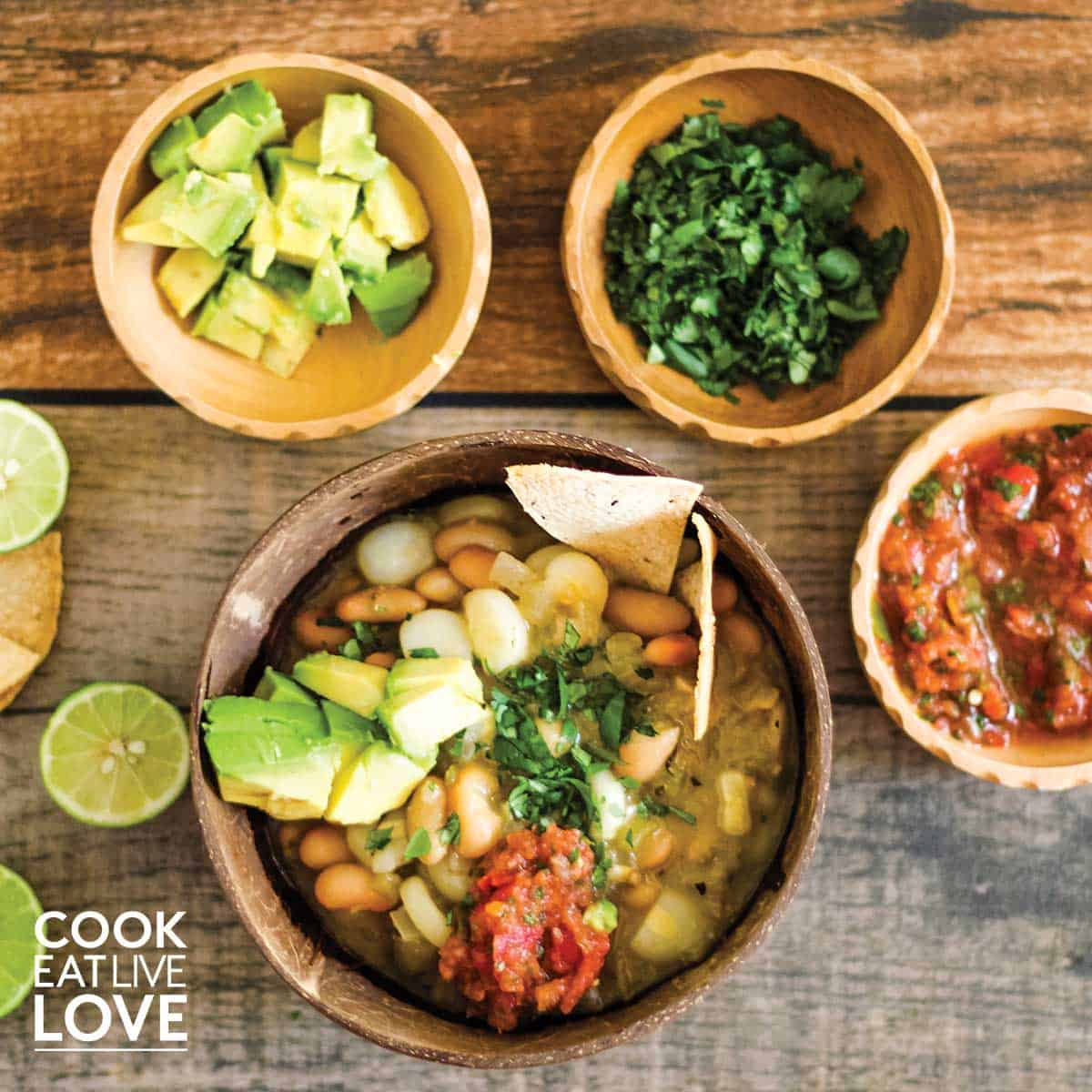 Overhead photo of bowl of white bean chili ready to eat. Shown with some topping ideas including avocado, cilantro and salsa.