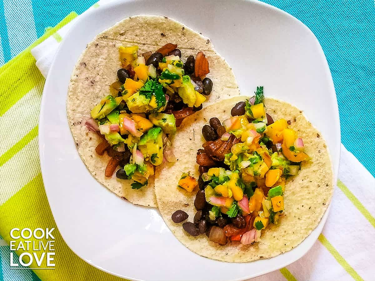 Black bean and mango tacos on white plate.