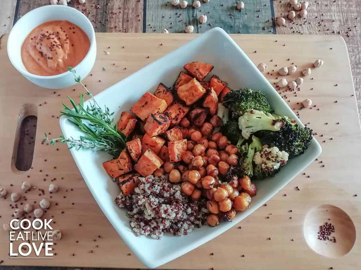 White square bowl showing sweet potatoes quinoa roasted chickpeas and broccoli.