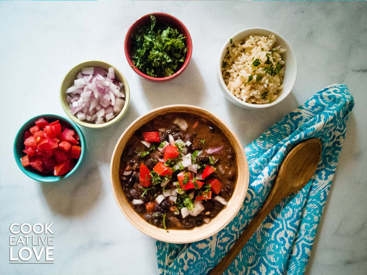 Bowl of creamy black beans along with a bowl of rice and other toppings.