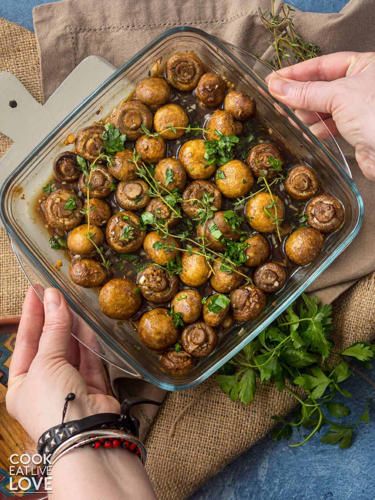 Hands setting dish of oven roasted mushrooms on the table