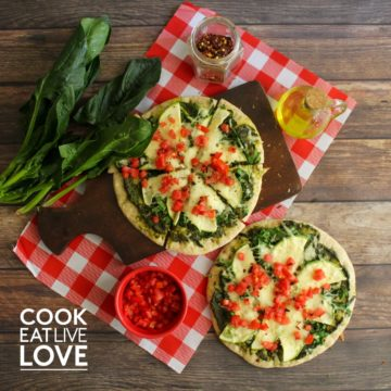 Two pesto and veggie pizzas on a table