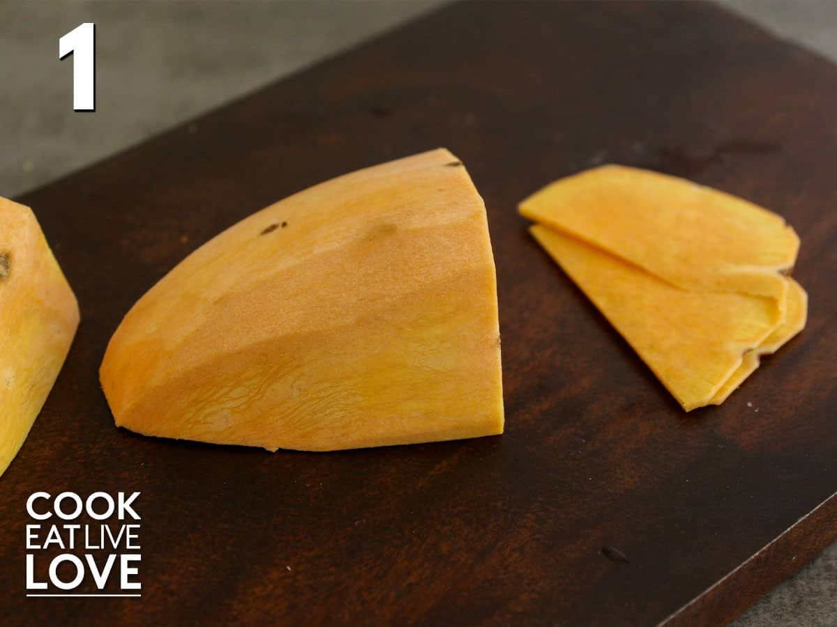 Sweet potato is cut in half and flat side is facing the bottom so it doesn't slip, cutting into thin slices.