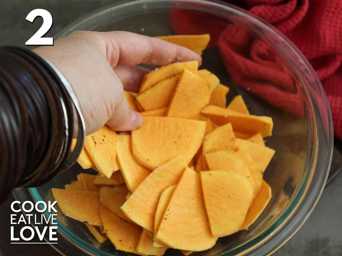 Sweet potatoes are in a glass bowl being tossed around with hand to distribute the salt and pepper.