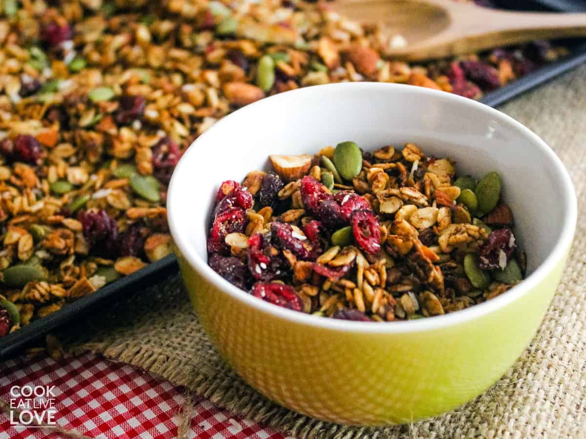 Vegan granola in a bowl with baking tray in background