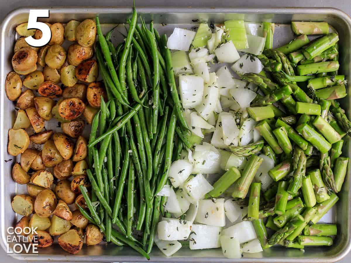 Adding the veggies to the baking tray with the potatoes