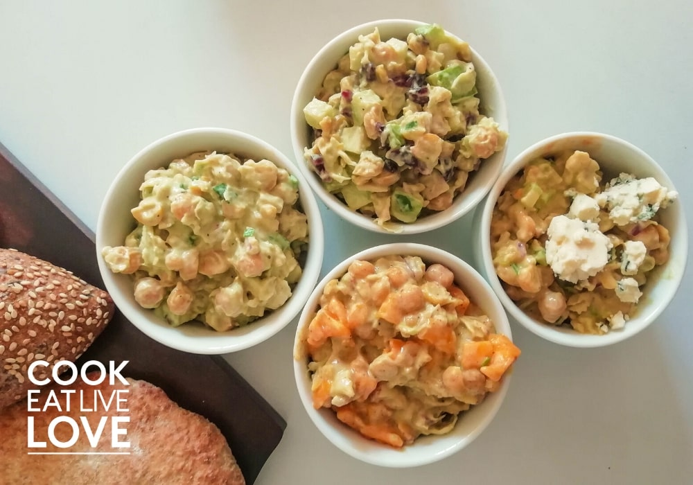Four different flavors of creamy chickpea salad in white bowls on white background .