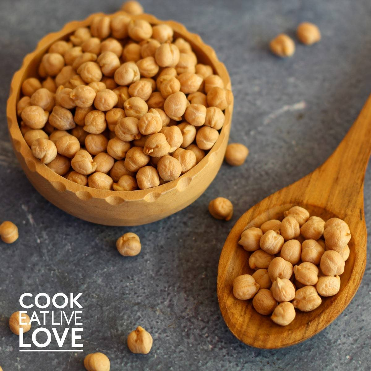 Chickpeas in a bowl on table with wooden spoon