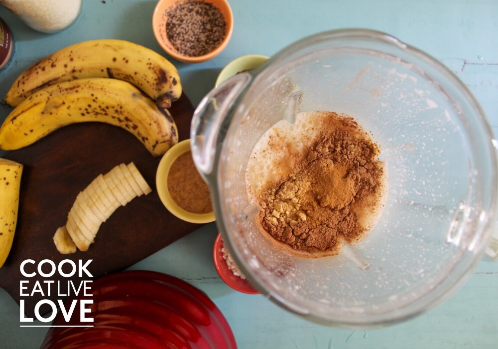 Overhead shot of blender with milk, cacao, maca and other ingredients  bananas cut on the side