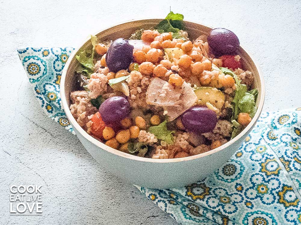 Bulgur chickpea bowl in a gray bowl on blue patterned napkin.