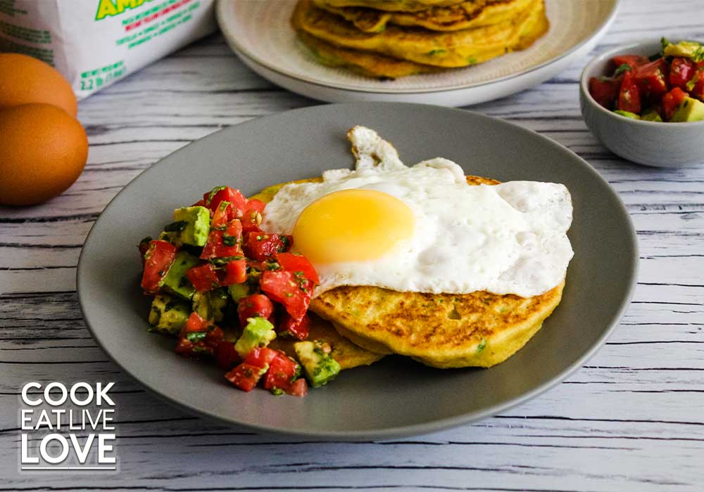 Savory corn pancakes are on a plate topped with fried egg and tomato and avocado salad on the side in the background are whole eggs and bag of masa harina.