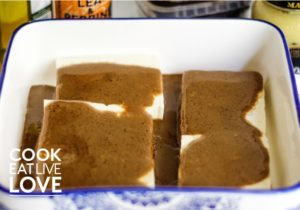 Marinade is poured over tofu in dish.