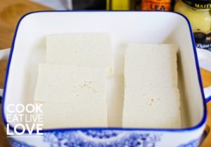 Tofu is shown in a single layer in baking dish ready to marinate.