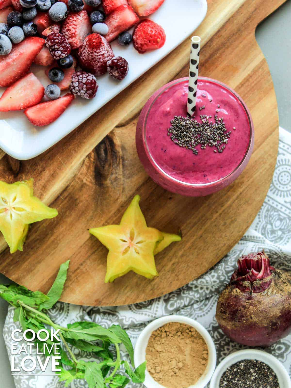 Smoothie on a table surrounded by berries