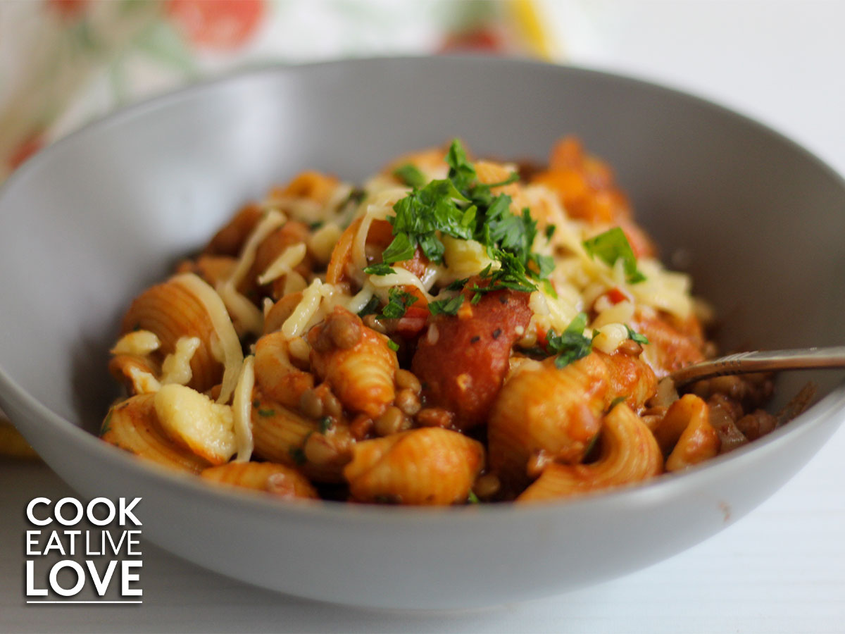 Closeup of lentil chili pasta in gray bowl with digging into pasta for a bite.