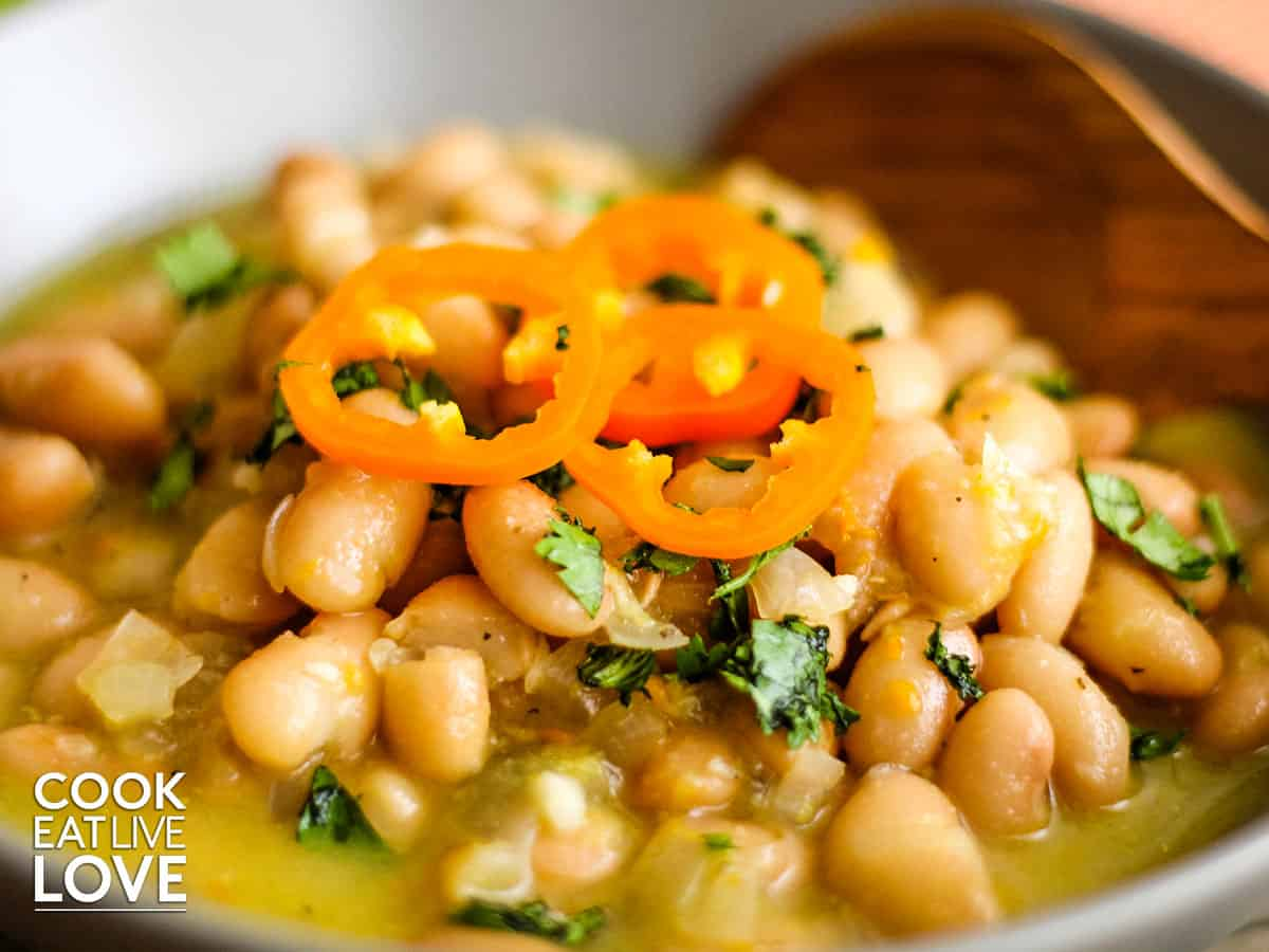 Closeup on bowl of peruvian beans garnished with aji amarillo slices.