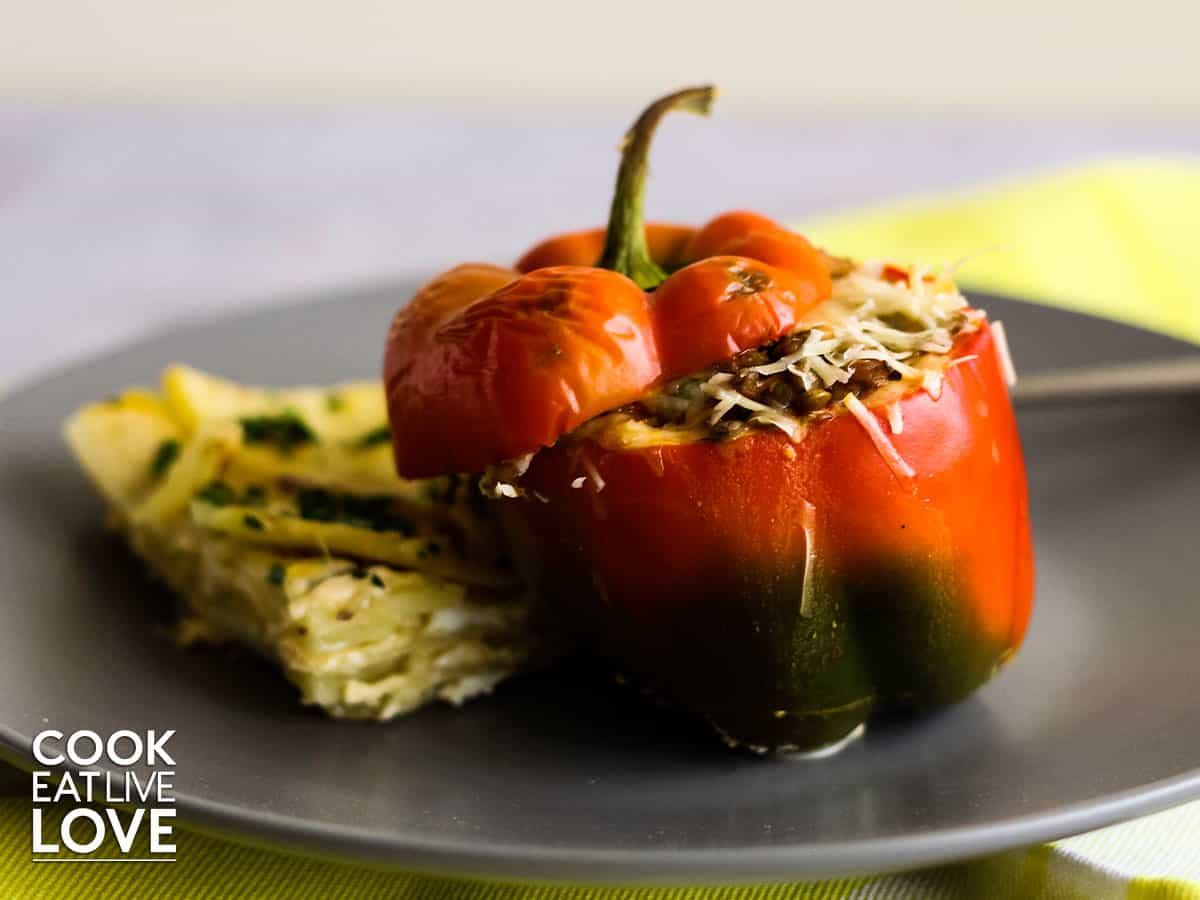 Stuffed pepper is served on a gray plate along with a layered potato casserole side dish