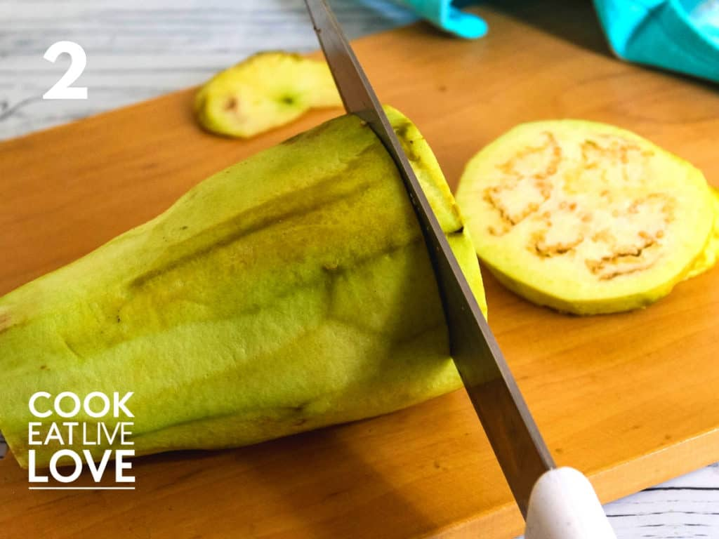 Peeled eggplant is on a cutting board and a knife is shown cutting it into slices.
