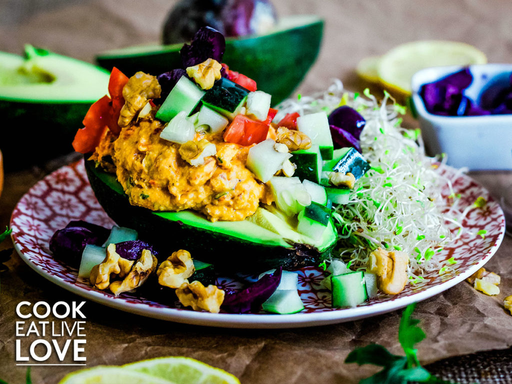 Close up of avocado boat on a red and white plate. Half an avocado is topped with roasted red pepper hummus and tons of fresh vegetables. Sprouts on the side.  In the back of plate are vegetables used to make the dish.