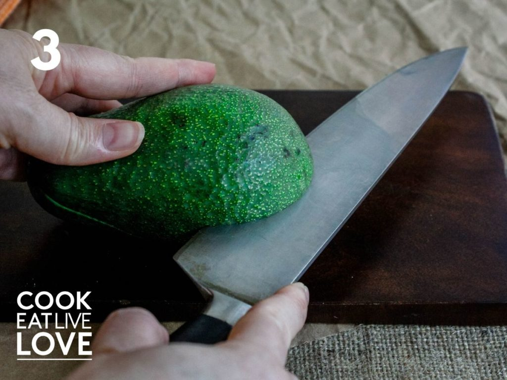 The avocado has been rotated so the knife is now cutting the other end of the avocado.